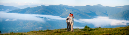 Sweety couple hikers covered with a blanket standing together on a hill, enjoying beautiful mountain landscape with morning haze over the mountains and forests. Panorama Stock Photo