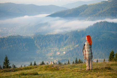 Red-haired woman covered with a blanket standing on a hill, enjoying beautiful mountain landscape with morning haze over the mountains and forests. Copy space