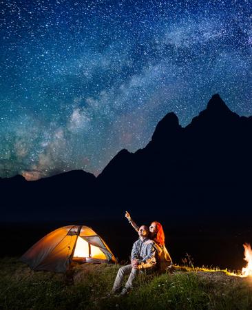fogatas: turistas joven hombre y una mujer mirando el cielo estrellado brilla en la noche. Feliz pareja sentada cerca de la tienda y fogata. vía láctea y las montañas en el fondo Foto de archivo