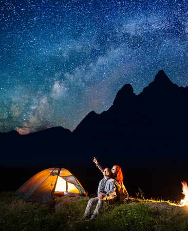 Young tourists man and woman looking at the shines starry sky at night. Happy couple sitting near tent and campfire. Milky way and mountains on the background Archivio Fotografico