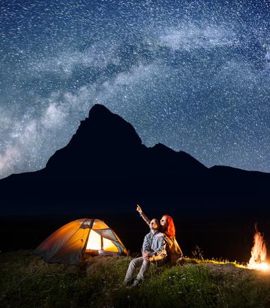 Mochileros chica y chico mirando el cielo estrellado brilla en la noche. Pareja joven sentado cerca de la tienda y fogata. vía láctea y las montañas en el fondo