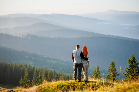 Couple standing on a hill, enjoying beautiful mountain landscape with morning haze over the mountains and forests. Guy embracing red-haired girl, she is covered with a blanket. Back view. Copy space Stock Photo