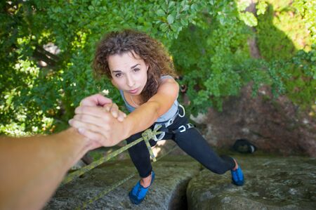 rockclimber: A brave rockclimber is helping a fearless female climber to reach a top of mountain. Man giving a hand to the woman. Teamwork