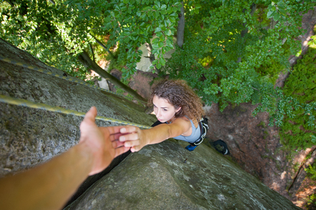 rockclimber: Young fearless woman climbing on big rock, and trying to catch helping hand. Top view. Extreme sports concept