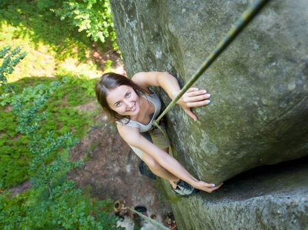 Beautiful woman climbing on a rocky wall with rope, bouldering. Smiling and looking towards the camera. View from the top