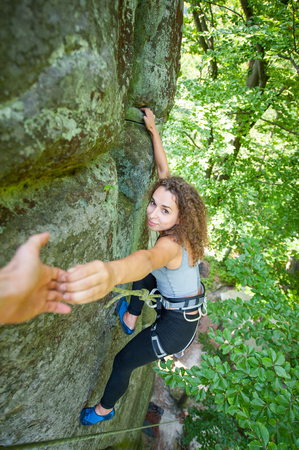 A male climber is helping a young beautiful female rockclimber. Man giving a hand to the woman. Climbing equipment