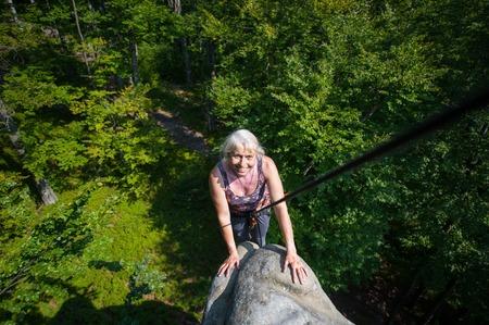 rockclimber: Smiling woman rockclimber is reaching top of the rock. Climbing equipment