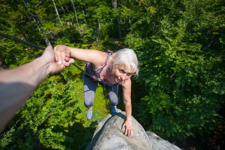 Older woman climbing on high rock, her male partner giving her a helping hand Stock Photo