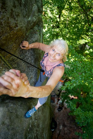 rockclimber: A belayer is helping to smiling older female climber to reach a peak of rock. Man giving a hand to the woman. Top view
