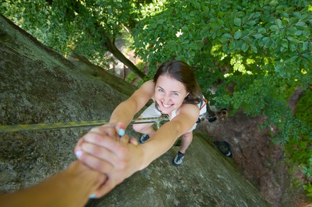 Young happy female climber hanging on two hands on high boulder. Man giving a helping hand to reach a peak of mountain