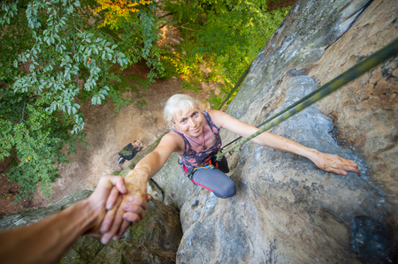 Strong male rockclimber is helping a older female climber to reach a peak of the rock. Man giving a hand to the woman. View from the top Stock Photo