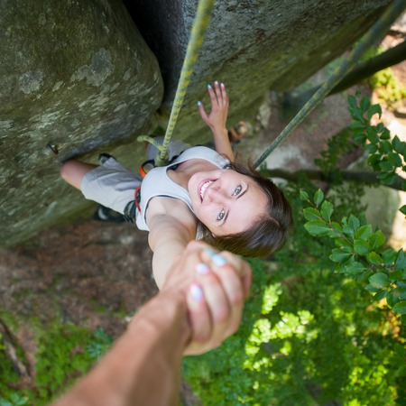 rockclimber: A strong man rockclimber is holding a happy female climber by hand on a rocky wall. View from the top. Climbers teamwork