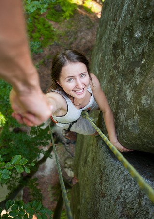 rockclimber: A brave male rockclimber is holding a fearless woman climber by hand on a rocky wall. View from the top. Helping hand
