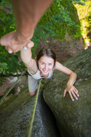 rockclimber: Athletic male rockclimber is holding a beautiful female climber by hand on a rocky wall. View from the top. Extreme sports concept