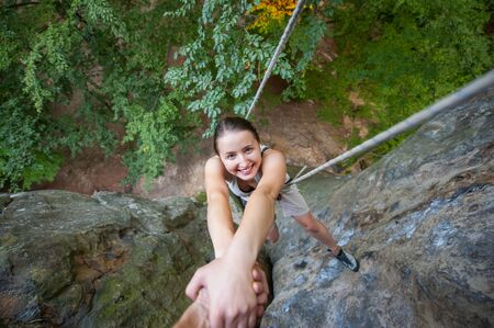 Male rock climber is holding a happy female climber by hands on a high rocky wall. View from the top. Extreme sports concept