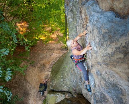 Brave older woman rock climber is climbing with carbines and rope on a rocky wall. Belayer standing on the ground insuring the climber. View from the top. Extreme sports concept
