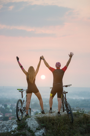 lifted hands: Magnificent sunset, bright sun between cyclists on the cliff top. Silhouette of guy and girl on mountain bikes keep the hands lifted upwards. Pink Kinesio tape glued on the girls hand