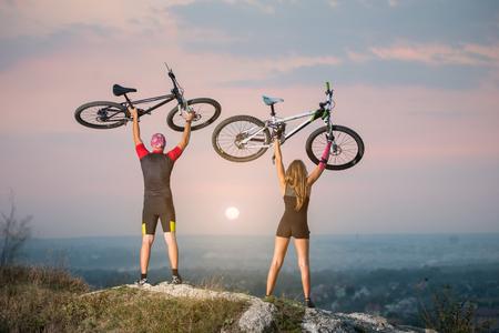 mujer deportista: El hombre y la mujer que sostienen los ciclistas de bicicletas de alta en el cielo en la cima de una colina contra magnífica puesta de sol con el fondo borroso. rosada de la cinta Kinesio pegado en la mano de la chica.
