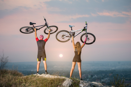 high up: Man and woman bikers holding bikes high up in the sky on the top of a hill against magnificent sunset with blurred background. Pink Kinesio tape glued on the girls hand. Stock Photo