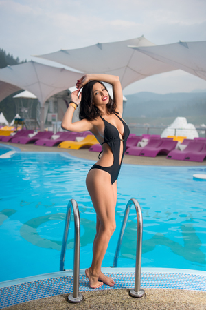 Attractive smiling female in the black swimsuit with shapely body is posing near the swimming pool at the resort Stock Photo