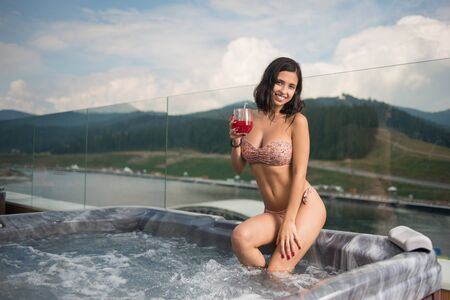 woman in bikini sitting at the Jacuzzi with cocktail