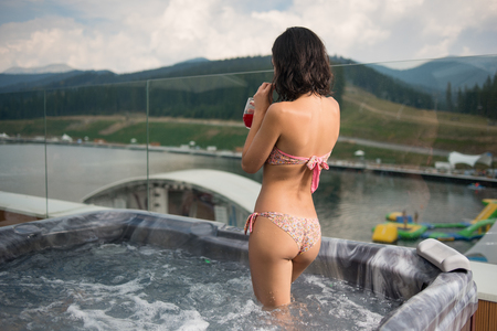 Back view brunette girl in bikini drinking cocktail, standing at the Jacuzzi outdoors on vacation against blurred background of nature and cloudy sky