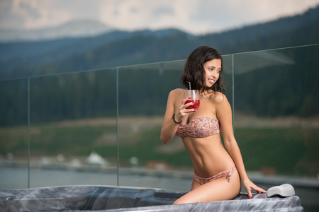 Sensual woman with perfect body in bikini sitting at the Jacuzzi with cocktail and looking away against blurred background of nature Stock Photo