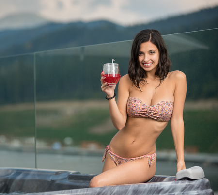 Portrait of happy attractive girl with perfect body in bikini sitting at the Jacuzzi with cocktail, smiling and looking to the camera against blurred background of nature