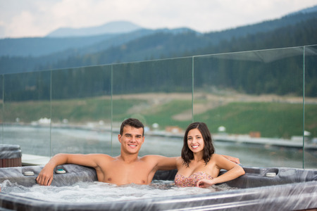 Young couple relaxing enjoying jacuzzi hot tub bubble bath outdoors on romantic vacation against blurred background of river, forest and hills Фото со стока