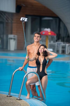 Beautiful couple - guy and girl with perfect figure posing against the swimming pool with perfect aqua water and taking selfie photo with monopod on the luxury resort Stock Photo
