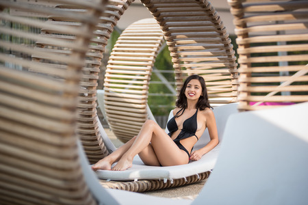 Gentle lady sitting in black bikini on original wooden lounger with white mattress among other similar sunbeds on the luxury resort.