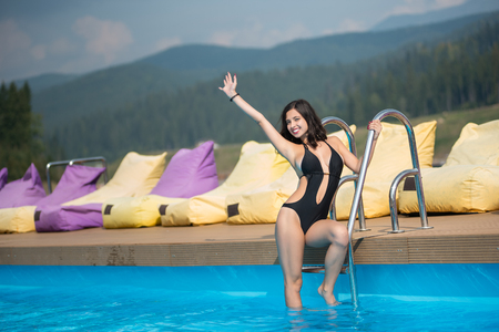 Young happy woman in black bikini is posing in the swimming pool on mountain resort. On the background hills and forest in the distance Stock Photo