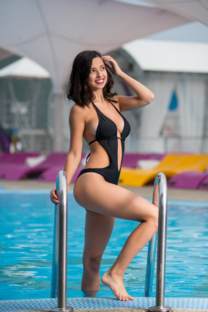 Attractive smiling female in the sexy black swimsuit with shapely body is posing near the swimming pool at the resort with blurred background Stock Photo