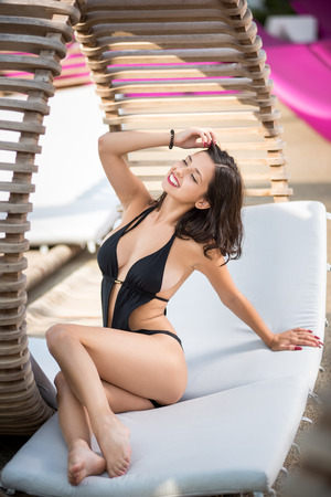 Beautiful young female with snow-white smile in a black bikini lying propped on her hands on a wooden lounger at the luxury resort