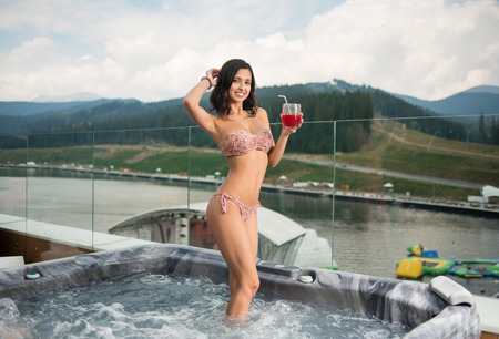 Beautiful female in bikini standing with cocktail at the Jacuzzi outdoors on vacation against blurred background of nature and cloudy sky Stock Photo