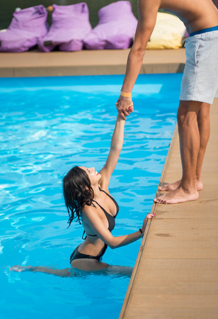 Beautiful woman in black swimsuit in the swimming pool holding a mans hand trying to get out at sunny day, blurred background