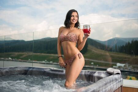 Sexy lady in bikini standing with cocktail at the Jacuzzi outdoors on vacation against blurred background of nature and cloudy sky