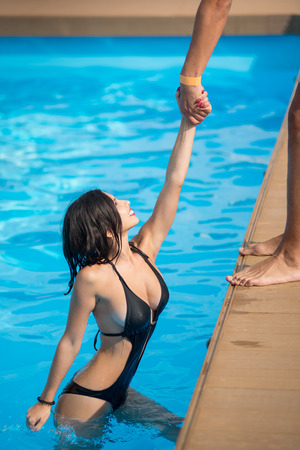 Smiling female in black bikini in the swimming pool holding a mans hand trying to get out at sunny day at the resort