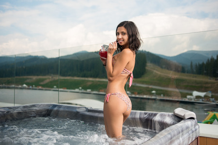 Back view of happy girl in bikini standing with cocktail at the Jacuzzi outdoors on vacation against blurred background of nature and cloudy sky Stock Photo