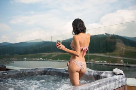 Back view brunette girl in bikini standing with cocktail at the Jacuzzi outdoors on vacation against blurred background of nature and cloudy sky
