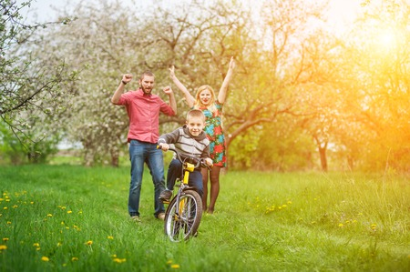 Happy child riding bicycle while his joyful parents celebrating success of his son. Family having fun against the blooming trees, dandelions and fresh greenery in spring garden