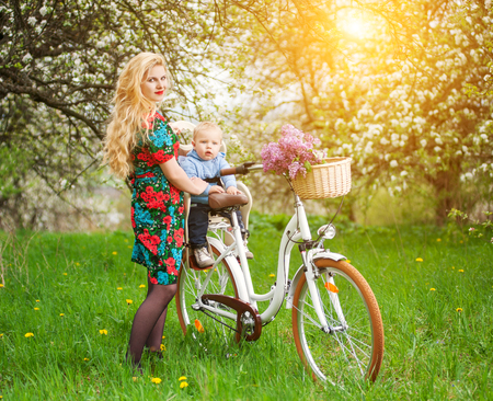 Young blonde mother with long hair and red lips in flowered dress holding son in bicycle chair, in the basket lay a bouquet of lilacs, against of blooming trees, dandelions in spring garden Stock Photo