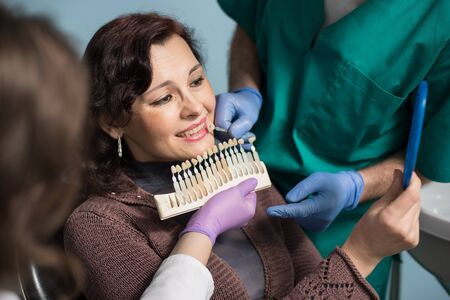 treating: Dentist with assistant and female patient checking and selecting colour of the teeth in dental clinic office. Doctor is making the process of treatment. Dentistry Stock Photo