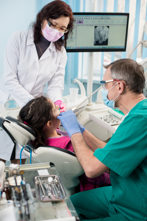 Young girl with on the first dental visit. Senior pediatric dentist with nurse treating patient teeth at the dental office. On the background screen with X-ray the patients teeth. Dental equipment Stock Photo