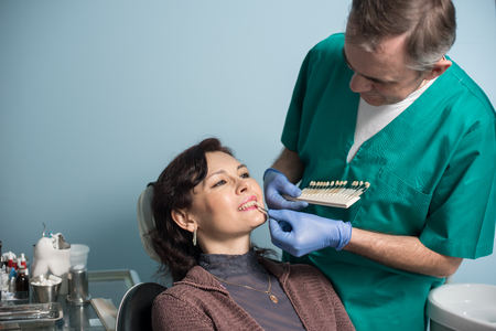 treating: Dentist and female patient checking and selecting colour of the teeth in dental clinic office. Doctor making the process of treatment. Dentistry Stock Photo