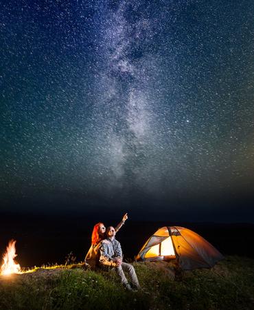 Dos amantes - chica y chico mirando el cielo estrellado brilla en la noche. Amorosa pareja sentada cerca de la tienda y fogata. Larga exposición Foto de archivo