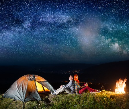 Romantic couple sitting by bonfire near glowing tent under incredibly beautiful starry sky. On the background luminous village in the valley. Astrophotography Stock Photo