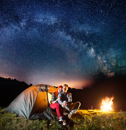 Night camping. Romantic couple sitting in front tent near campfire under shines starry sky and Milky way. Long exposure