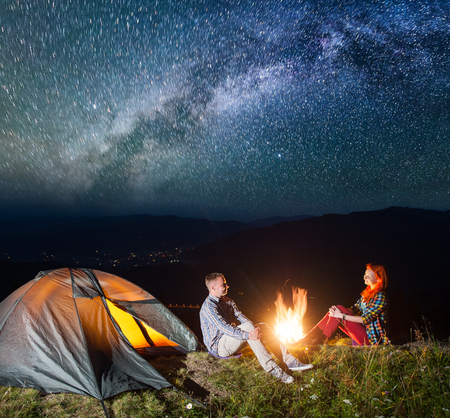 Night tent camping. Happy couple tourists sitting by campfire under incredibly beautiful starry sky and Milky way
