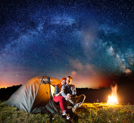 Night camping. Charming couple tourists sitting in front tent near campfire under shines starry sky and Milky way